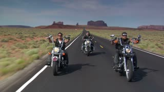 Three Bikers On A Redrock Desert Highway