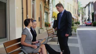 Three business people talking outside on a park bench