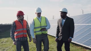 Three electrician workers standing in solar power station and discussing something using digital tablet