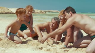 Three gengrations of one family are resting on the beach. They are playing with sand and pouring it.