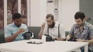 Three men on sofa in living room having fun in vr glasses