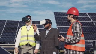 Three men standing in solar power station and using virtual reality glasses. Copyspace