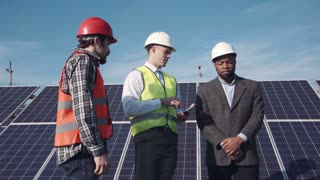 Three mixed race men standing in solar power station and discussing something using digital tablet for visualization