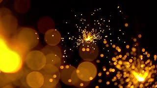 Three orange sparklers against dark background. Super slow motion shallow focus video, 500 fps