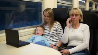 Three passengers in th train in the evening. Mother and son watching movie on computer, grandmother having a phone talk