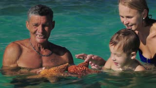 Three people in sea water. Local man showing woman and her son two big starfish, child touching them