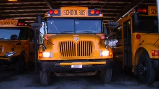Three School Buses Parked In Garage