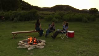 Three Women Sit Around A Campfire