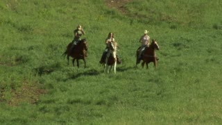 Three Young Women On Horses Gallop Across Green Meadow- Toward Camera