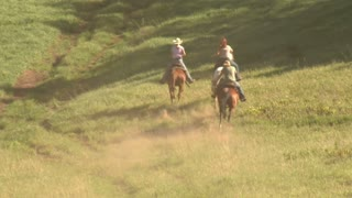 Three Young Women On Horses Gallop Across Green Meadow–with Dust