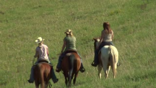 Three Young Women On Horses Ride Across Green Meadow-  Zoom Out