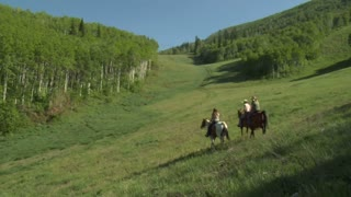 Three Young Women On Horses Ride Across Green Meadow