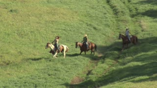 Three Young Women On Horses Walk Across A Trail