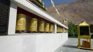 Tibetan Buddhist prayer wheels in Buddhism temple. Man traveler turns Tibetan Buddhist prayer wheels. India. Tabo Spiti Valley, Himachal Pradesh, India.