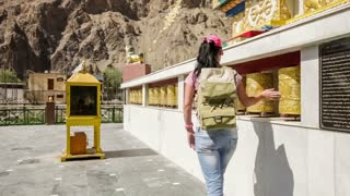 Tibetan Buddhist prayer wheels in Buddhism temple. Woman traveler turns Tibetan Buddhist prayer wheels. India. Tabo Spiti Valley, Himachal Pradesh, India.