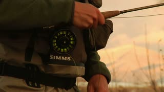 Tight Shot Of Hand On Flyfishing Reel While Casting