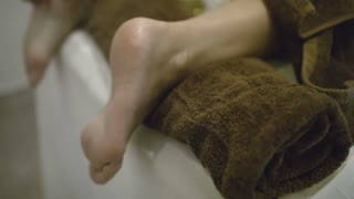 Tilt and pan close-up shot of spa stone massage of female legs at beauty treatment salon. Health and body care
