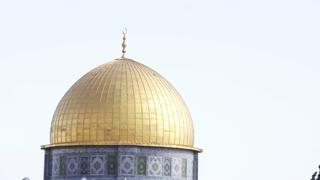 Tilt From Golden Dome To Men Praying