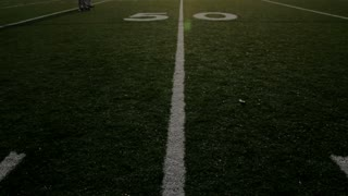 Tilt up on a high school football stadium at the 50 yard line.
