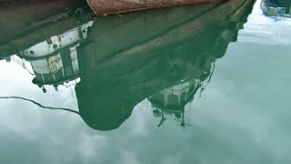 Tilt Up Reflection Of Tug Boat In Water