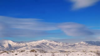 Time Lapse clouds over white wintry mountains
