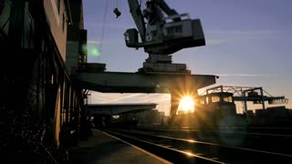 time lapse. cranes industrial industry. sunset dusk sun flare
