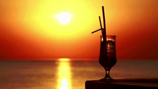 Time lapse of a glass with cocktail and tubules on sunset background. Cocktail at sunset. Sea sunset time lapse. Vacations on sea. Sun sets over sea. Tropical bar. Beach party