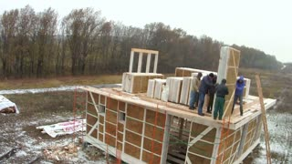 Time-lapse of construction house of straw bales. Work process in bad weather, installation of walls on the second floor