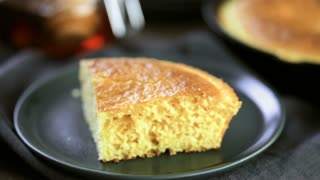 Time-lapse. Slice of sweet cornbread with honey on the plate.