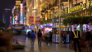 Time lapse, wide shot of pedestrians walking past stores on Nanjing Road at night, Shanghai, China