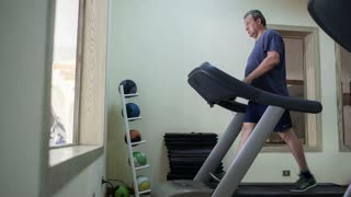 Timelapse of a senior man running on treadmill in hotel gym. Regular sports trainings help to keep fit and healthy