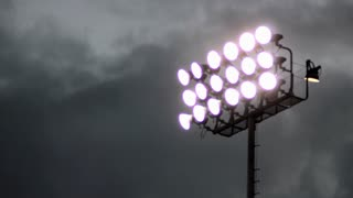 Timelapse of clouds moving fast behind stadium lights.