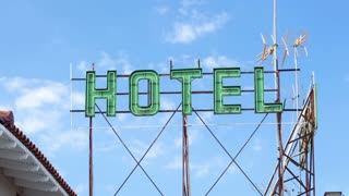 Timelapse of sun overshining green hotel banner and clouds moving in blue sky