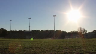 Timelapse of the sun setting over a football stadium.