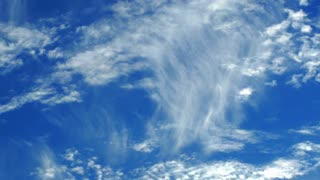 Timelapse shot of cirrus clouds against bright blue sky.