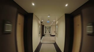 Timelapse steadicam and wide angle shot of moving along the empty light hotel corridor with pictures hanging on the walls