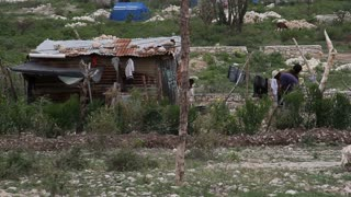 Tin Shack,  Clothes Line, And Residents In Haiti