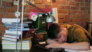 Tired student sleeping on desk after studying at home