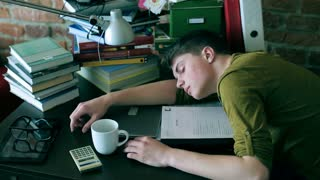 Tired student sleeping on desk and notes at home