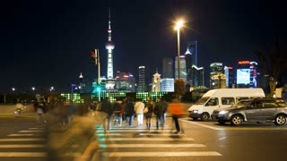 TL People crossing busy road in front of the new Pudong skyline, illuminated at night, the Bund, Shanghai, China