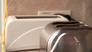 Toasted bread jumps out of the toaster - close up, slow motion shot at 240fps