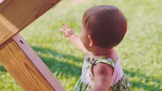 Toddler girl is pointing on something then smiling to the camera. Slow Motion 240 fps. Cute little happy baby girl is standing outdoors in a sunny garden. Happy childhood concept.