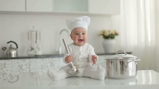Toddler sitting on a table with a saucepan and ladle