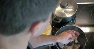 Top view of a man cooking dinner. He frying meat, turning it over on the pan. Lemon, salad and boiling water nearby