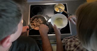Top view of young couple cooking at home. Man stewing meat in the pan, while woman making a sauce
