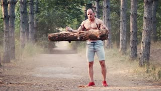 Topless strong muscular man doing biceps curls with log on forest road