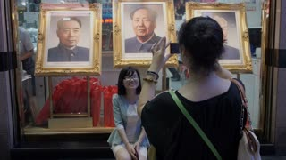 Tourist Takes Photo in Front of Mao Zedong Painting