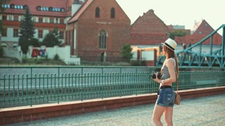 Tourist travel photographer taking pictures of a European city. Slow Motion, 4K. Beautiful hipster woman capturing moments of a morning city at sunrise on her digital camera. Travel. Lens flare.