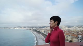 Tourist using app on smartphone at the vacation. Female wearing in red pullover at the seaside in mediterranean town. City view with sea beach sky seafront