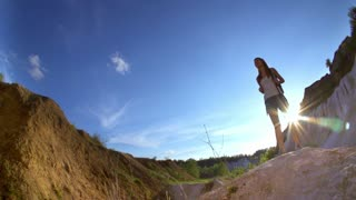 Tourist woman-hiker in mountains. Athletic cheerful woman-hiker is happy to reach the top and jumping up to celebrate her success in the sunny mountains. Slow motion filmed at 240 fps. Fish eye.